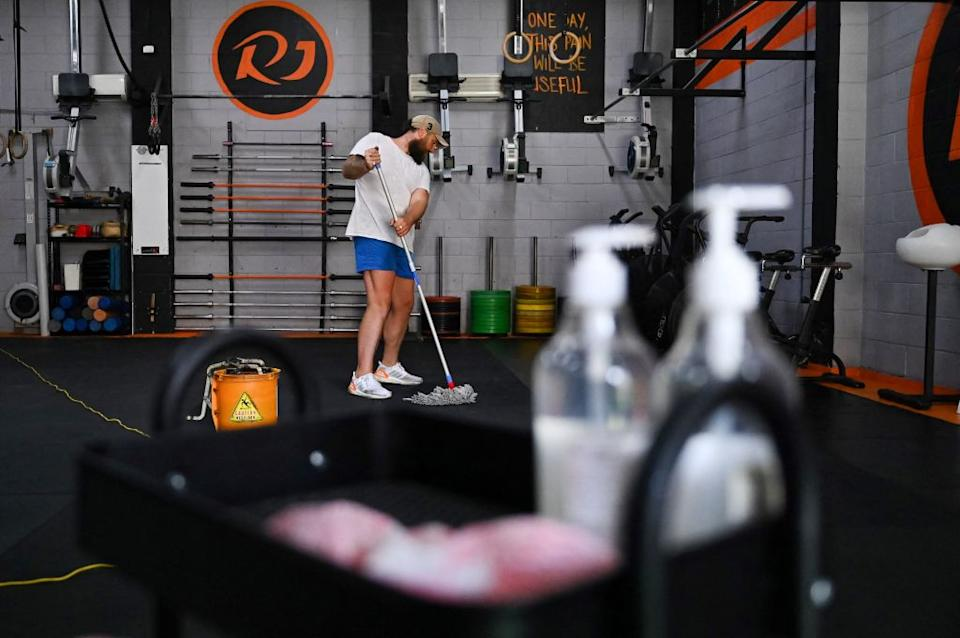 An employees of CrossFit RJ gym cleans and prepares a day before reopening due to the easing of COVID-19 restrictions in Sydney.