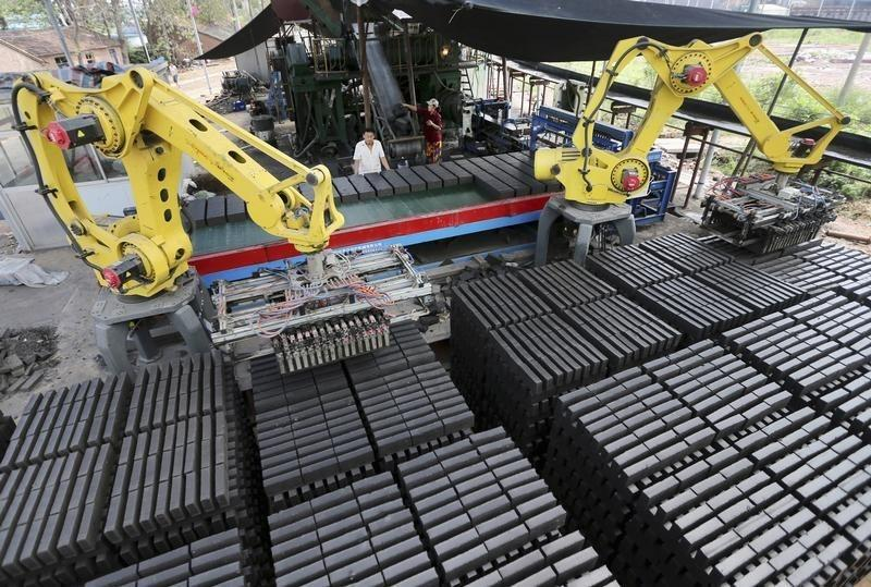 Workers look at machines moving newly made raw bricks at a factory in Huaibei