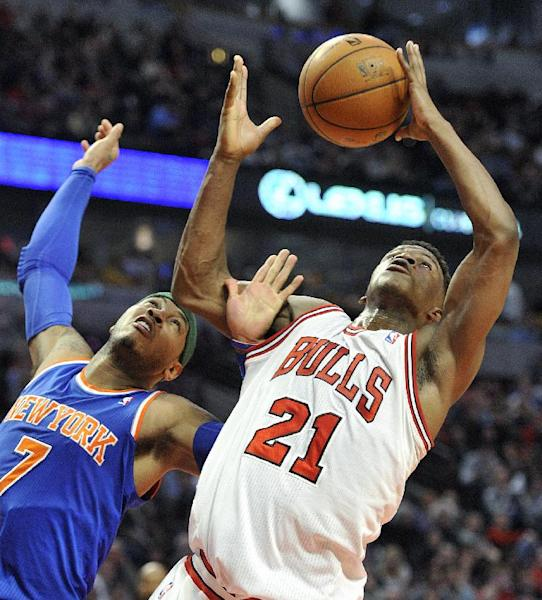 New York Knicks' Carmelo Anthony (7) and Chicago Bulls' Jimmy Butler battle for a rebound during the first half of an NBA basketball game, Thursday, April 11, 2013, in Chicago. (AP Photo/Jim Prisching)