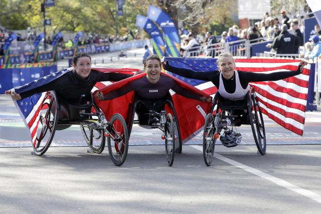 Manuela Schar, of Switzerland, center, winner of the pro wheelchair women's division of the New York City Marathon, is flanked by second place finisher Tatyana McFadden, left, of Clarksville, Md, and third place finisher Susannah Scaroni, of Tekoa, Wash., in New York's Central Park, Sunday, Nov. 3, 2019. (AP Photo/Richard Drew)