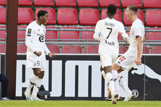 Lille's Jonathan David, left, celebrates with team mates after scoring his side's opening goal during a French League One Soccer match between Rennes and Lille at the Roazhon Park stadium in Rennes, France, Sunday Jan. 24, 2021. (AP Photo/David Vincent)