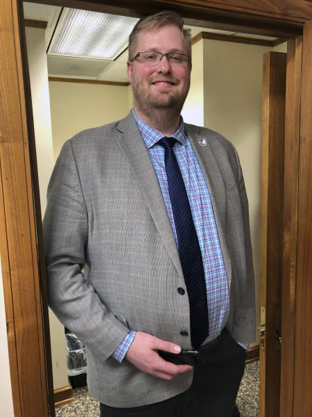 North Dakota Insurance Commissioner Jon Godfread poses for a portrait at the state Capitol in Bismarck, N.D., Thursday, March 28, 2019. Godfread, who claims he is 6-foot-11 3/4 inches, is challenging New York City councilman Robert Cornegy Jr., a 6-foot-10 councilman from Brooklyn's claim of being the tallest male politician in the world. Comegy was certified by Guinness World Records in January. But wait, Brad Sellers, a former Ohio State and Chicago Bulls star listed at 7 feet, also says he has a claim. Sellers is now the mayor of Warrensville Heights, Ohio. (AP Photo/James MacPherson).
