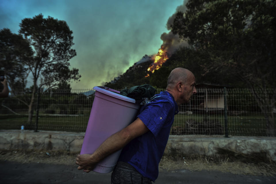 A man walks away as an advancing fire rages Hisaronu area, Turkey, Monday, Aug. 2, 2021. For the sixth straight day, Turkish firefighters battled Monday to control the blazes that are tearing through forests near Turkey's beach destinations. Fed by strong winds and scorching temperatures, the fires that began Wednesday have left eight people dead. Residents and tourists have fled vacation resorts in flotillas of small boats or convoys of cars and trucks.(AP Photo)