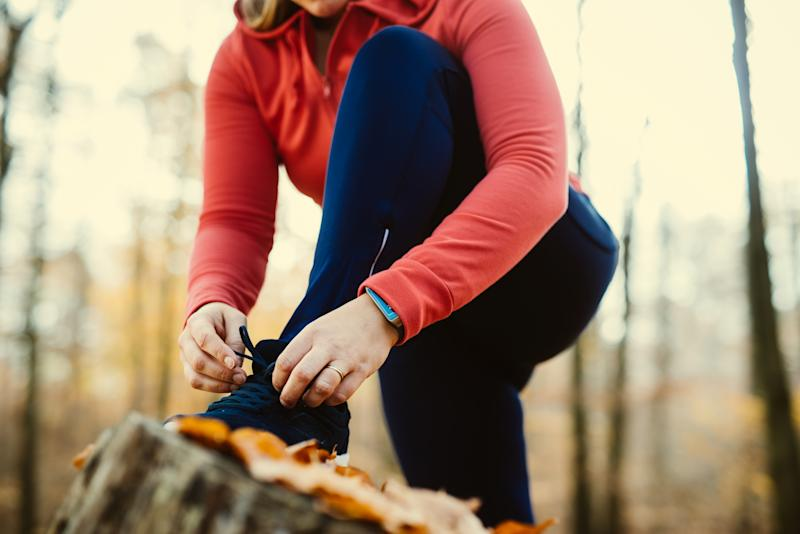 Woman fixing her shoelaces before jogging on a trunk.