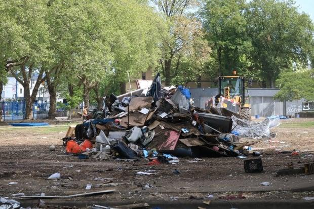 Crews remove debris from Oppenheimer Park in May 2020. As the pandemic took hold in B.C., officials forced park residents out, finding homes for many, while others found other places to go.