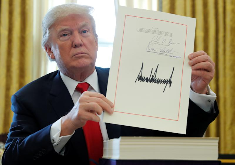 FILE PHOTO: U.S. President Donald Trump displays his signature after signing the $1.5 trillion tax overhaul plan in the Oval Office of the White House in Washington, U.S., December 22, 2017. REUTERS/Jonathan Ernst/File Photo
