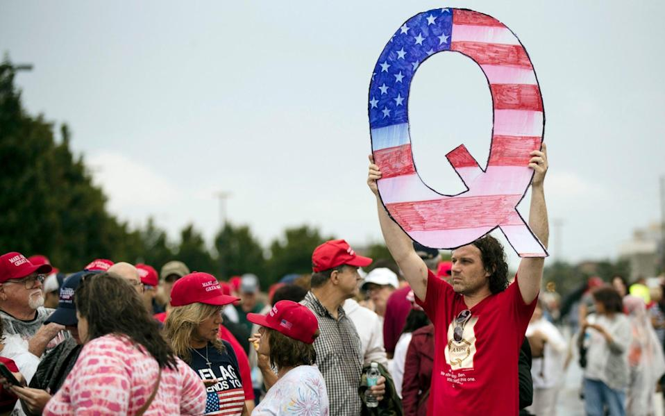 Protesters holds a Q sign waits in line with others to enter a campaign rally with President Donald Trump - Matt Rourke/Matt Rourke Source: AP