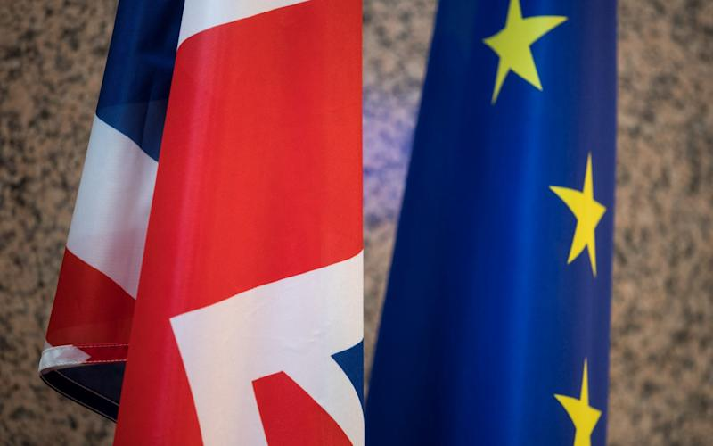 The Union flag, also known as the Union Jack, left, stands next to a European Union (EU) flag inside the Justus Lipsius building of the European Council in Brussels, Belgium, on Wednesday, March 29, 2017. - Bloomberg
