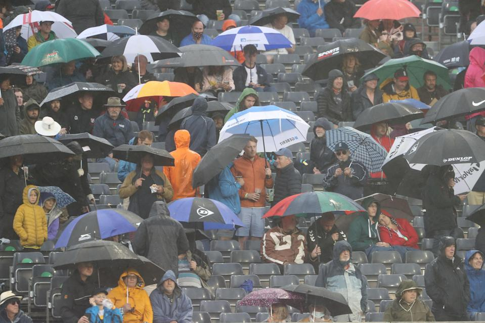 Fans try to evade the rain at Bristol on Sunday (AFP via Getty Images)