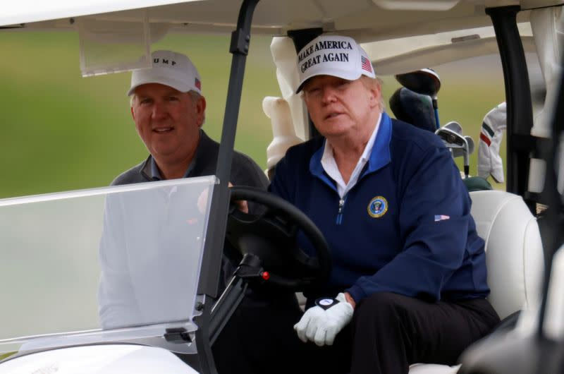 FILE PHOTO: U.S. President Donald Trump drives a golf cart at the Trump National Golf Club in Sterling