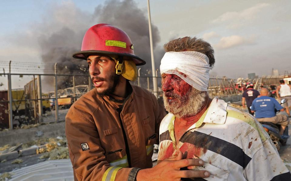 A firefighter helps a wounded man at the scene - GETTY IMAGES