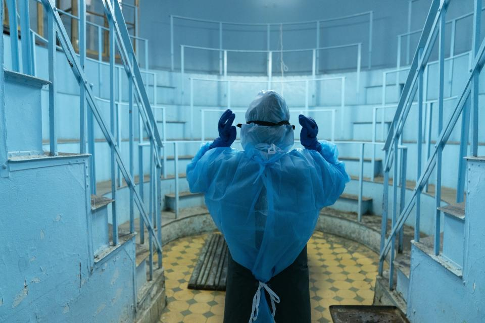 Olena Mazur, pathologist wearing special suits to protect herself against coronavirus, prepares to conduct an autopsy in an anatomical theater at the Lviv National Medical University in Lviv, Western Ukraine, on Tuesday, Jan. 5, 2021. A medical college in western Ukraine has been transformed into a temporary hospital as the coronavirus inundates the Eastern European country. (AP Photo/Evgeniy Maloletka)