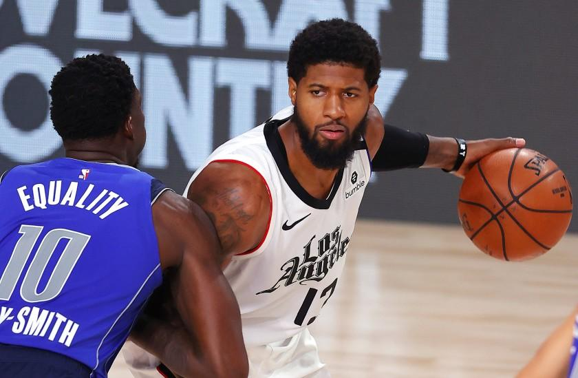 Los Angeles Clippers' Paul George, right, looks to pass against Dallas Mavericks' Dorian Finney-Smith (10) during the fourth quarter of Game 3 of an NBA basketball first-round playoff series, Friday, Aug. 21, 2020, in Lake Buena Vista, Fla. (Mike Ehrmann/Pool Photo via AP)