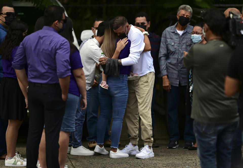 Jose Antonio Rodriguez, center right, is embraced as he arrives at a wake for his 27-year-old-daughter Keishla Rodriguez, whose lifeless body was found in a lagoon Saturday, at a funeral home in San Juan, Puerto Rico, Thursday, May 6, 2021. A federal judge on Monday ordered Puerto Rican boxer Felix Verdejo held without bail after he was charged with the death of Keishla Rodriguez and with intentionally killing the unborn child she was carrying. (AP Photo/Carlos Giusti)