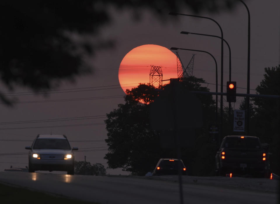 Traffic flows on Townline Road as a hazy sun sets in Vernon Hills, Ill,, Tuesday, Sept. 15, 2020. The smoke from dozens of wildfires in the western United States has now blanket much of the county along with parts of Mexico and Canada, as residents thousands of miles away on the East Coast are being treated to unusually hazy skies and remarkable sunsets. (John Starks/Daily Herald via AP)