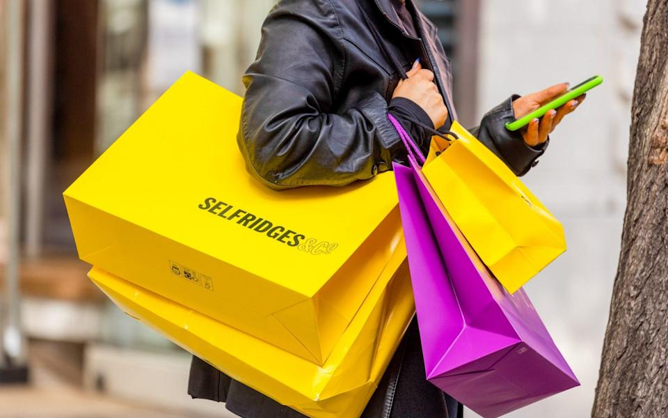 A shopper holds bags from the Selfridges & Co. Ltd. department store on Oxford Street in central London - Jason Alden/Bloomberg