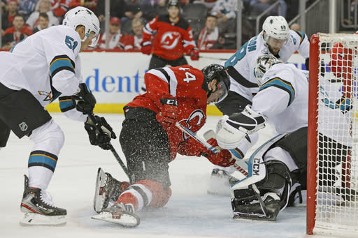 New Jersey Devils left wing Miles Wood (44) tries to shoot past San Jose Sharks goaltender Martin Jones, front right, as Sharks defenseman Radim Simek (51) and center Melker Karlsson (68) defend during the second period of an NHL hockey game, Thursday, Feb. 20, 2020, in Newark, N.J. (AP Photo/Kathy Willens)