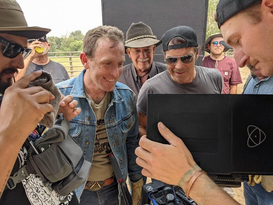 """Jay Pickett, center in sunglasses, reviews takes from his film """"Treasure Valley"""" as director Travis Mills, in denim jacket, and Canyon County Sheriff Kieran Donahue, in cowboy hat, look on. Pickett died while filming """"Treasure Valley,"""" which he wrote and starred in."""