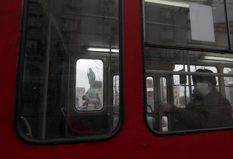 A man looks out of a window on a tram driving by the new monument of Stefan Nemanja on Sava Square in Belgrade, Serbia, Wednesday, Jan. 27, 2021. Serbia's President Aleksandar Vucic is to unveil a soaring monument of Stefan Nemanja, a 12th century Serbian ruler on Wednesday, Saint Sava Day. (AP Photo/Darko Vojinovic)