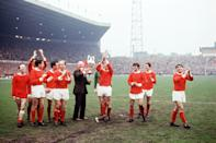 Manchester United manager Matt Busby (sixth l) holds the League Championship trophy aloft as he and his players parade it around Old Trafford: (l-r) Nobby Stiles, David Sadler (arms raised), Shay Brennan, John Aston, Denis Law (hidden), Bobby Charlton, Busby, Alex Stepney, Pat Crerand, George Best, Jimmy Ryan, Tony Dunne (Photo by PA Images via Getty Images)