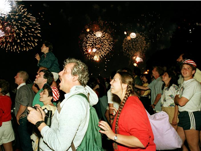 Crowds of people at New York's Battery Park react to the fireworks display over the Statute of Liberty on July 4, 1986.