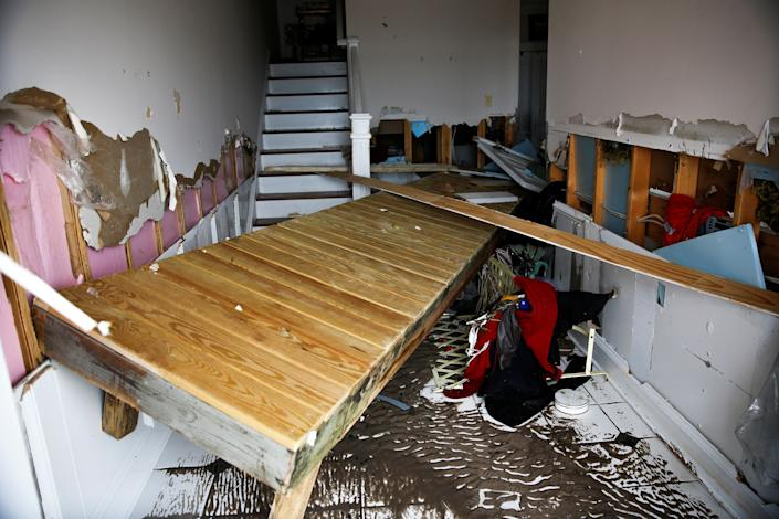 Part of a dock remains inside of a house as people clean their properties after the pass of Hurricane Florence in New Bern, North Carolina.