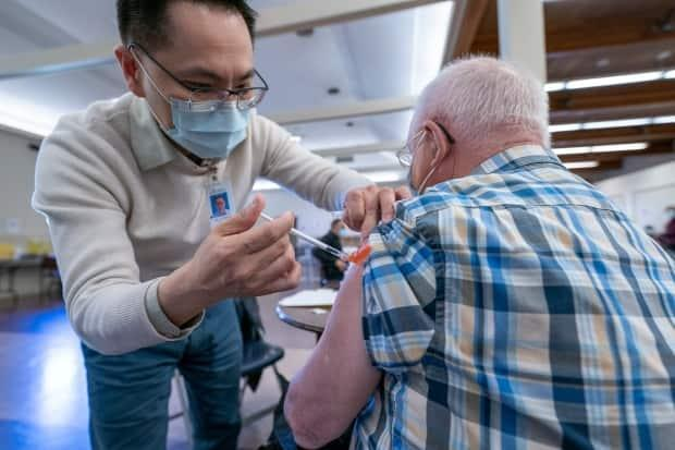 Dr. E. Kwok administers a COVID-19 vaccine to a recipient at a vaccination clinic run by Vancouver Coastal Health, in Richmond, B.C., in April 2021.  (Jonathan Hayward/Canadian Press - image credit)