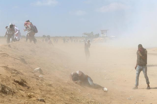 <p>Palestinian demonstrators react to tear gas fired by Israeli forces during a protest marking the 70th anniversary of Nakba, at the Israel-Gaza border in the southern Gaza Strip, May 15, 2018. (Photo: Ibraheem Abu Mustafa/Reuters) </p>