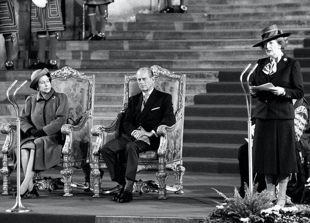 The Queen looks on as Margaret Thatcher speaks at a Commonwealth conference in 1986