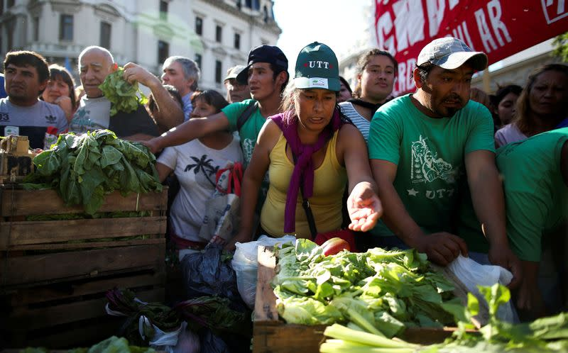 FILE PHOTO: People grab lettuce during a farmers' protest against low prices in Buenos Aires, Argentina, in February 2019