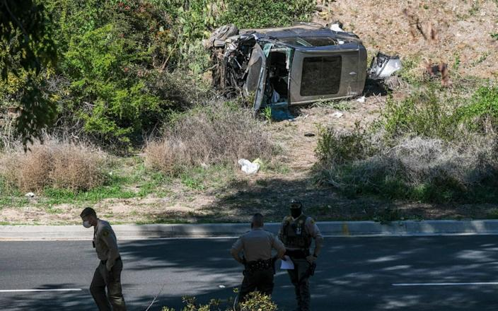 A vehicle rests on its side after a rollover accident involving golfer Tiger Woods along a road in the Rancho Palos Verdes section of Los Angeles - AP