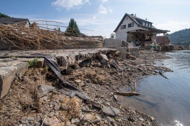 A house completely destroyed by flooding stands on the banks of the Ahr in Insul, Germany, in July. Extreme events are raising alarm bells about the impact of climate change. (Boris Roessler/dpa via Associated Press - image credit)