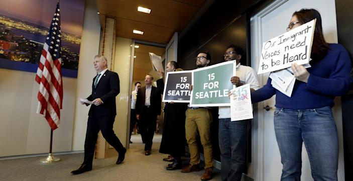 Seattle Mayor Ed Murray, left, walks into a news conference past supporters and opponents of a proposal to increase the minimum wage in the city Thursday, April 24, 2014, in Seattle. The mayor said his advisory group of business, labor, non-profits and other representatives have not yet agreed on a plan to increase the minimum wage to $15 an hour. (AP Photo/Elaine Thompson)