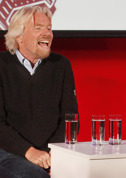 """Virgin Group owner, British billionaire Richard Branson smiles to students packing a hall at Warsaw University as he tells them that they need to be """"passionate about whatever you are doing in life"""" to achieve success during a launch of Virgin Academy, a project to help young Poles start their businesses in Warsaw, Poland, on Wednesday, Oct. 24, 2012. Branson also said that the launch of his space travel project Virgin Galactic keeps being pushed back. (AP Photo/Czarek Sokolowski)"""
