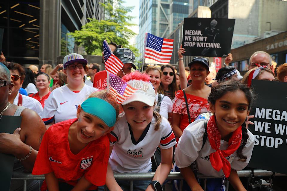 Fans holds flags and signs as they turn out to honor the U.S. women's soccer team for a ticker tape parade along the Canyon of Heroes, Wednesday, July 10, 2019, in New York. (Photo: Gordon Donovan/Yahoo News)