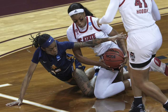 North Carolina A&T's Deja Winters, left, and North Carolina State's Jada Boyd, right, battle for a loose ball during the first half of a college basketball game in the first round of the women's NCAA tournament at the University Events Center in San Marcos, Texas, Sunday, March 21, 2021. (AP Photo/Chuck Burton)
