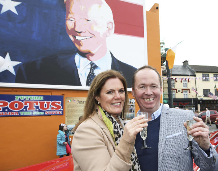 Joe Blewitt, a cousin of US Presidential candidate Joe Biden, and his wife Deirdre celebrate in anticipation of the results of the US election as Biden edges closer to victory over Donald Trump, at a mural of Biden in his ancestral home of Ballina, Co. Mayo, Ireland, Saturday, Nov. 7, 2020. (AP Photo/Peter Morrison)