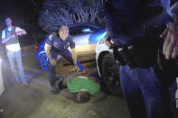 FILE - In this May 10, 2019 image from Louisiana State Trooper Lt. John Clary's body camera video, Trooper Kory York stands over Ronald Greene lying on his stomach outside of Monroe, La. The video shows Louisiana state troopers stunning, punching and dragging Greene as he apologizes for leading them on a high-speed chase. More than a year and a half after Louisiana state troopers were captured on body camera video brutalizing Greene during his fatal arrest, police brass were still trying to blame his death on a car crash at the end of a high-speed chase. (Louisiana State Police via AP)