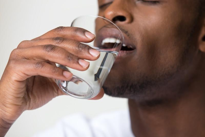 man holding glass drinking water