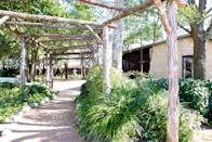 <p><strong>How did it strike you on arrival?</strong><br> With a large inviting porch, the two-story main house sits in a residential neighborhood. Several nearby cottages are also part of the hotel.</p> <p><strong>What's the crowd like?</strong><br> Couples of all ages, plus groups of women weekending in Fredericksburg.</p> <p><strong>The good stuff: Tell us about your room.</strong><br> I stayed in the Ivy, a bright white room with a queen bed and private porch with rocking chairs. With a vaulted ceiling and natural light, the room feels airy and spacious.</p> <p><strong>How about the little things, like mini bar, or shower goodies. Any of that worth a mention?</strong><br> No mini bar, but the room has a kitchenette with a coffee maker and mini fridge with bottled water.</p> <p><strong>Please tell us the bathroom won't let us down.</strong><br> In a nod to Hill Country, the bath products are lavender. The bathroom has a step-in shower.</p> <p><strong>Room service: Worth it?</strong><br> Breakfast is included in the rate and left at your door at 9 each morning. Presented in a picnic basket, it is delicious and fresh. The menu changes daily—quiche (still hot when delivered), fresh breads, eggs florentine, sausage,and fruit. A limited room service menu includes a cheese plate ($15), charcuterie plate ($15), and tea service ($8).</p> <p><strong>Staff: If you could award one a trophy, who gets it, and why?</strong><br> The staff is extremely attentive and friendly.</p> <p><strong>Anything else you'll remember or that you loved?</strong><br> In the main house, there are often fresh baked chocolate cookies to grab on your way in or out. There's also a lending library with books and DVDs.</p> <p><strong>Bottom line: worth it, and why?</strong><br> Upscale bed and breakfast that's a short walk to Main Street but far enough away to offer seclusion.</p>