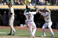 Oakland Athletics' Starling Marte, center, celebrates with Mark Canha, right after they scored on a double by Matt Olson, next to San Diego Padres' Tim Hill, left, during the 10th inning of a baseball game in Oakland, Calif., Wednesday, Aug. 4, 2021. The A's won 5-4. (AP Photo/Jed Jacobsohn)