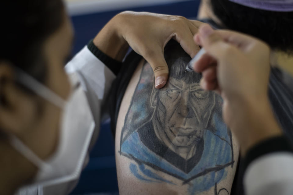 A man gets a shot of the AstraZeneca vaccine for COVID-19 in his arm covered by a tattoo of Star Trek's Spock character during a vaccination campaign for people over age 35 in Rio de Janeiro, Brazil, Friday, July 23, 2021. (AP Photo/Bruna Prado)