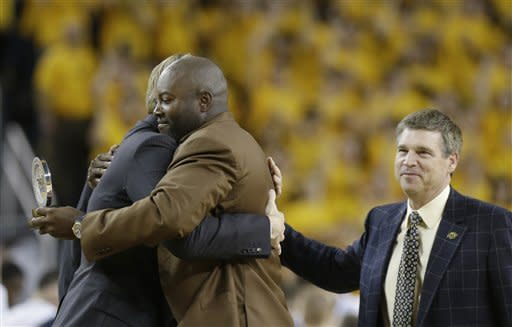 Glen Rice, center, hugs a teammate as athletic director Dave Brandon, right, pats his back during the first half of an NCAA college basketball game between Michigan and Penn State at Crisler Center in Ann Arbor, Mich., Sunday, Feb. 17, 2013. Rice received an award as a Top 75 All-Time March Madness Player. (AP Photo/Carlos Osorio)