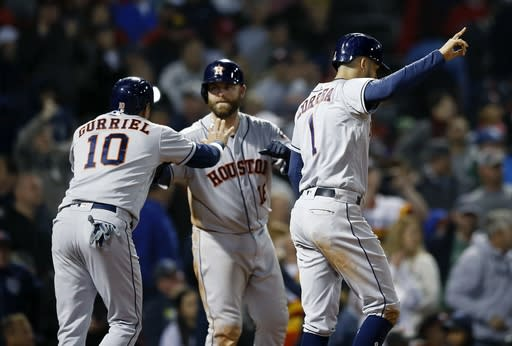 Houston Astros' Carlos Correa (1) and Yuli Gurriel (10) celebrate after scoring on a two-run double by Tyler White during the sixth inning of a baseball game against the Boston Red Sox in Boston, Sunday, Sept. 9, 2018. (AP Photo/Michael Dwyer)