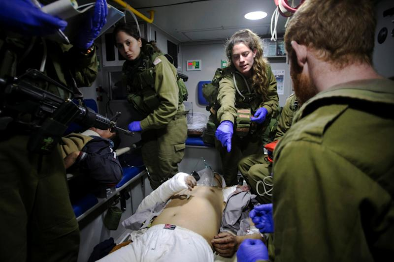 Israeli soldiers give initial medical treatment to wounded Syrians in the Israeli-occupied Golan Heights on 18 January 2017: REUTERS
