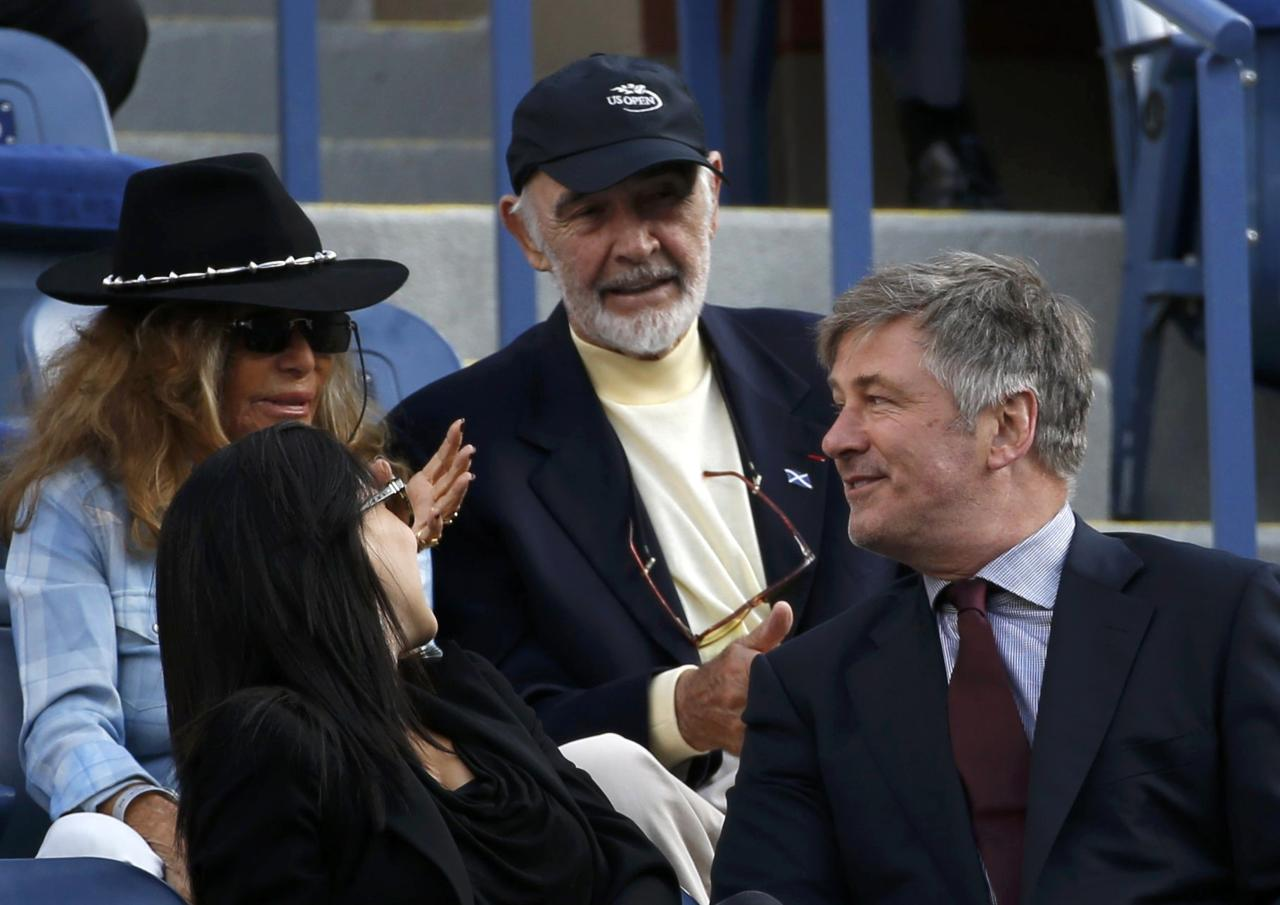 Actors Alex Baldwin (R) and Sean Connery (C) chat as they watch Rafael Nadal of Spain face Novak Djokovic of Serbia in the men's final match at the U.S. Open tennis championships in New York, September 9, 2013. REUTERS/Mike Segar (UNITED STATES - Tags: SPORT TENNIS ENTERTAINMENT)