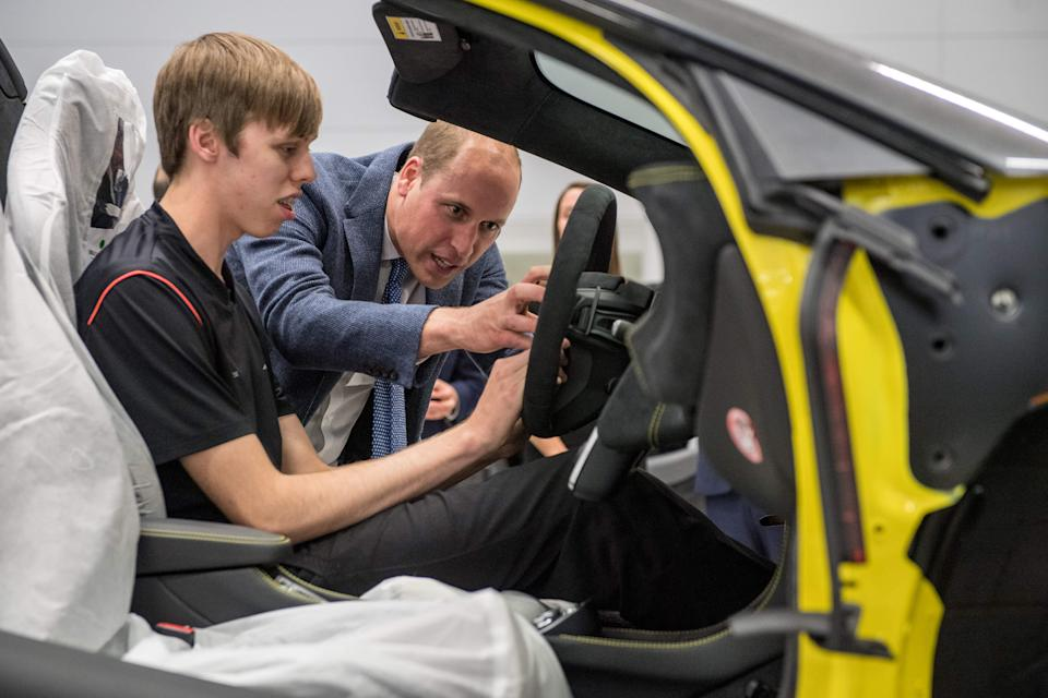 Britain's Prince William, Duke of Cambridge (R) helps fit an airbag to a McLaren car with apprentice of the year nominee, Alex Machin on the factory floor in Woking, west of London on September 12, 2017, during his visit to McLaren Automotive Production Centre. During the visit the Duke toured the technology centre and production centre where he got to see McLaren cars throughout the years as well as walk the factory floor to view the building of their commercial cars and speak to employees. / AFP PHOTO / POOL / CHRIS J RATCLIFFE        (Photo credit should read CHRIS J RATCLIFFE/AFP via Getty Images)