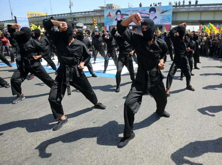 Iraqi Shiite fighters from the Iran-backed Hezbollah brigades take part in a military parade to mark the pro-Palestinian Al-Quds (Jerusalem) Day in Baghdad in May this year