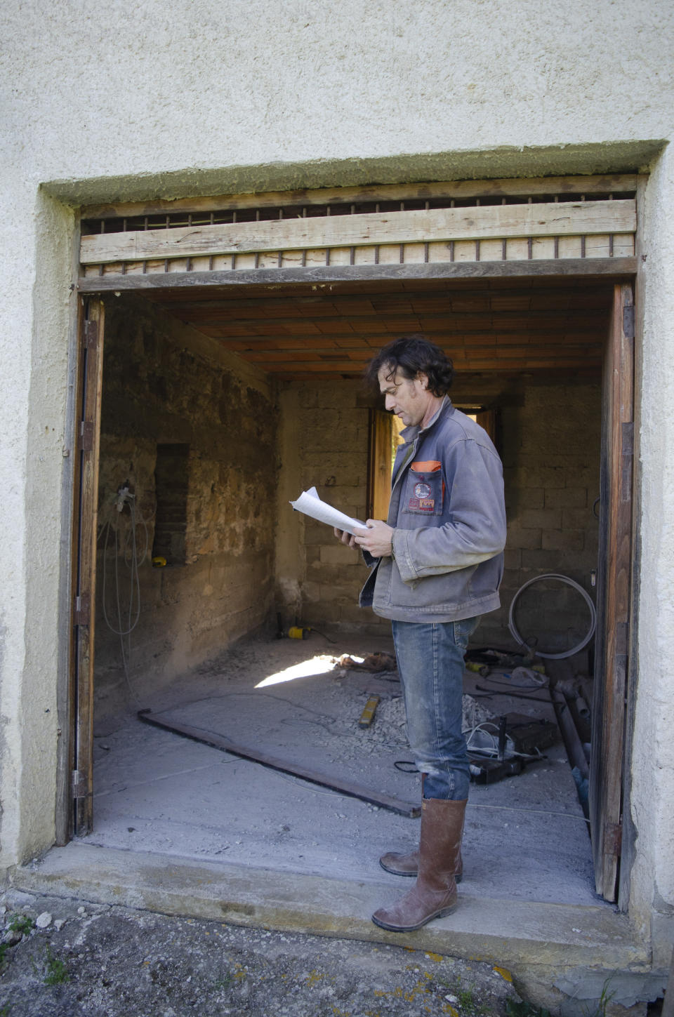 Cain Burdeau studies plans electrical circuits he plans to install at a country home he is renovating in Castelbuono, Sicily, on April 8, 2021. (AP Photo/Audrey Rodeman)