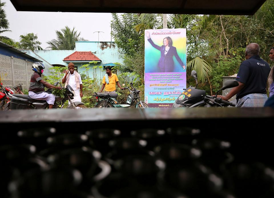 <p>Indian villagers gather outside a local eatery next to a banner featuring US vice president-elect Kamala Harris with a message wishing her best, in Thulasendrapuram, the hometown of Harris' maternal grandfather, south of Chennai, Tamil Nadu state, India.</p> (AP)